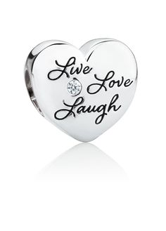 """Engraved with words """"Live, Love, Laugh"""", and featuring a single cubic zirconia, this beautiful sterling silver heart charm would make a sentimental gift. Exclusive to Emma & Roe."""
