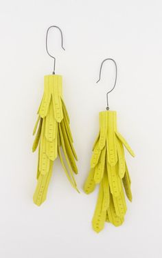 Giant Earrings by Claire McArdle Hand cut and hand etched, these bright yellow rolled leather tassle earrings have an oversized oxidised sterling silver hook
