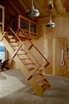 Inside Hood Canal Boat House, the ground level features a wooden storage unit, concrete flooring and plywood paneling. By Hoedemaker Pfeiffer Retractable Stairs, Space Saving Staircase, Loft Stairs, Deck Stairs, Roof Deck, Garage Loft, Journal Du Design, Tiny Cabins, Canal Boat