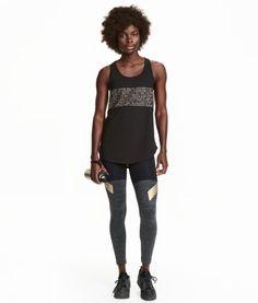 Graumeliert/Schwarz. Sporttights aus schnelltrocknendem Funktionsmaterial. Die Tights hat einen Druck auf dem Bein und einen breiten elastischen Bund.
