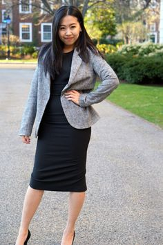 woman wearing grey blazer and black work dress for corporate attire, skirt the ceiling skirttheceiling.com