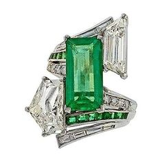 This dynamic, large-scale, adaptation of the classic platinum bypass ring is designed around a vivacious, bright green, elongated emerald-cut emerald weighing carats. The emerald is asymmetrically framed by two large fancy-cut diamonds: an epaulet-cu Emerald Jewelry, Gems Jewelry, Art Deco Jewelry, Diamond Jewelry, Jewelry Accessories, Fine Jewelry, Jewelry Design, Emerald Rings, Emerald Diamond