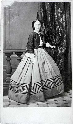 Civil War Carte de Visite Photographed By Remington's, New York This carte de visite shows a woman wearing the most fashionable apparel of the early 1860s. For the first time, women wore skirts and blouses, although the blouse is covered with a jacket. That the skirt is deeply pleated and extends more to the back than from the front probably dates it around 1865. The skirt is trimmed with starkly contrasting trimming in a Greek key design, which was very stylish. The jacket was most likely…