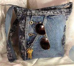 Sac à main tout en jean dans les tons de bleu uni et imprimé marine et blanc avec bandoulière ajustable. Lintérieur du sac est doublé en toile de jean bleu uni et on y trouve une poche zippée. Le sac se ferme par une fermeture à glissière . Deux poches au dos dont une zippée et une