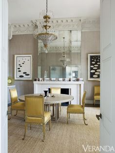 Antiqued mirrored panels nod to the past.  Chairs, Cove Landing, in Claremont silk. Jansen chandelier. Mantel and linen on walls, both custom. Art, Alexander Calder. INTERIOR DESIGN BY VEERE GREENEY
