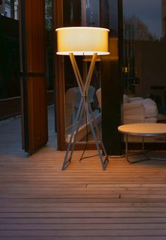 The Cala 140 Outdoor Floor Lamp features a living room-worthy shade atop intersecting iron or wood legs, echoing a metal café table or painter's trestle.