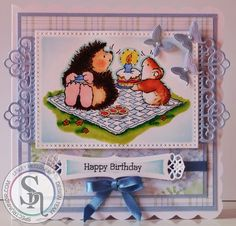 Designed by Lesley McCloskey.  Stamp is Penny Black Hedgehog birthday. Coloured with Spectrum Noir pens and pencils -  hedgie - EB3, EB6, EB8, FS1, FS3, CR1, PP1, PP3, EB1, 089, 103 and 034 mouse - TN1, TN2, TN4, TN5, PP1, 089, 091 and 034 grass and flowers - CG2, CG3, JG1, GB5, DR1 and 047 blanket - TB1 cake - TB1, TB4, DR1, TN1, TN2, CT2, CT4, GB5, IG1, 067 and 086 tarts - IG1, DR1, GB1 and GB2 cup - TB1, TB3 and 067 sky - IB1.  #spectrumnoir #pennyblack #hedgehog #birthday #handmade…