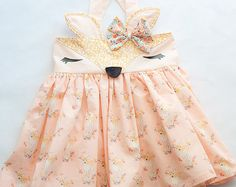 Foxy Fox is a high waist suspender skirt featuring a fox face waistband, vinyl eyes, felt nose and hand sewn bow.  The straps are fixed with elastic and has 2-3 buttons on the back closure. Available in sizes 12mo to 10. Matching Foxy Fox handmade doll available in Dolls listing.  Current turn around time is 4 weeks.and black fox face. This skirt is available in sizes Babies 12mos, 18mos Toddlers 2t, 3t, 4t Girls 5, 6, 7, 8, 9, 10  My shipping time states that this may take up to four weeks…