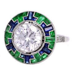Vintage deco [style] engagement ring makes a gorgeous statement of love and devotion, with beautiful romantic details and gorgeous craftsmanship. Finely crafted in solid platinum, it is centered with 1 stunning genuine round diamond approx.2.25 ct. The center stone is displayed in a unique design that is accented with 18 genuine French cut Colombian emeralds and 18 genuine French cut sapphires; millgrain borders