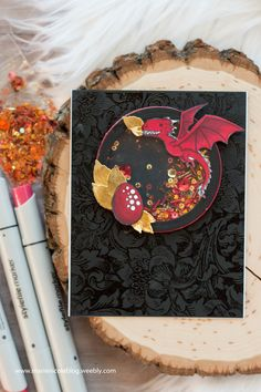 FABULOUS dragon shaker card! Stamps and shaker bits from Kindred Stamps. Brutus Monroe background embossed in clear powder. Marie Nicole Designs.