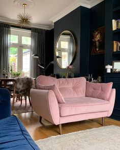 Dark inky navy blue living room with pink velvet sofa and distressed Turkish rug. Large round brass West Elm mirror and brass mid century Sputnik pendant. Dark interiors in a period property Blue And Pink Living Room, Blue Velvet Sofa Living Room, Navy Blue Living Room, Rugs In Living Room, Living Room Chairs, Home And Living, Living Room Designs, Living Room Furniture, Navy Blue Velvet Sofa