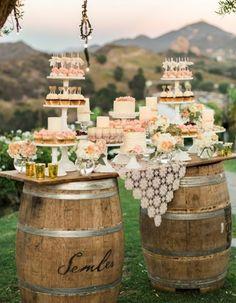 mariage champetre decoration, tonneaux en bois et planche en bois en guise de table, petits gateaux, cupcakes, présentoir gateau, nappe motifs floraux, cocktails, déco florale, paysage montagnard