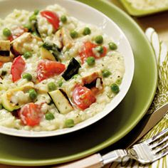Creamy Parmesan risotto is accented by hearty vegetables and chicken in this delicious dinner recipe via Woman's Day