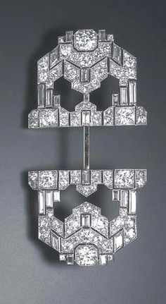 AN ART DECO DIAMOND JABOT PIN  The openwork geometric plaque set with old European and baguette-cut diamonds, joined by a gold pin to a terminal of similar design, mounted in platinum and 18k gold, circa 1935