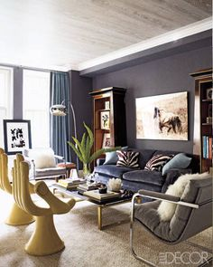 """In the den, vintage Pedro Friedeberg """"hand"""" chairs, Milo Baughman armchairs upholstered in a Holland & Sherry wool flannel, and a sofa originally from Stark's childhood apartment surround a vintage cocktail table from Flair, and the walls are sheathed in a Lelièvre fabric.   - ELLEDecor.com"""