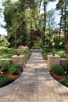 A back paving brick walkway to a raised planter with pillars and wing walls creates a beautiful focal point from the back of the house.