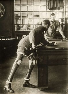 A soldier who lost both his legs in the first World War, playing a game of billiards, 1915.