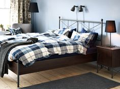 Ein Schlafzimmer mit MUSKEN Bettgestell in Braun, KUSTRUTA Bettwäsche-Sets blau Karo, flach gewebtem MORUM Teppich in Dunkelgrau und HEKTAR Wand-/Klemmspot