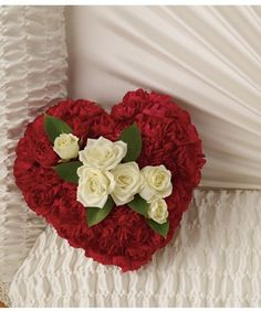 """""""Casket Heart."""" The most personal of all funeral piece,the miniature heart is placed inside the casket of solid carnations to form a smooth base with baby's breath and a ribbon."""