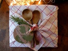 Neat gift wrap idea!  Wrap and tie a kitchen towel around a box or cookbook, add a couple of wood spoons, gift tag, and garnish, and voila!  A sweet package!