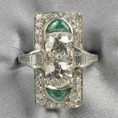 Art Deco Platinum, Emerald, and Diamond Ring, set with two old European-cut diamonds weighing 1.00 and 1.05 cts., further set with baguette- and single-cut diamonds, approx. total wt. 2.90 cts., fancy-cut emerald accents, millegrain and engraved details, size 7 1/2.