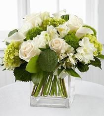 Inspire them with pristine blooms bursting with radiant light. Garden Hydrangea, calla lilies, roses, lisianthus and Peruvian Lilies are perfectly beautiful accented wtih the lush vibrant greens. Seated in a clear glass square block vase, this...