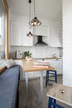 W tej klasycznej białej kuchni efektownie prezentują się industrialne dodatki – podwójna lampa nad barowym stołem i taborety na metalowych nogach. Te ostatnie w dodatku wprowadzają do wnętrza kolor. Przestrzeń pod oknem bez parapetu zagospodarowano praktycznym siedziskiem z półkami pod spodem.