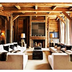 A gorgeous Chalet living room, so cozy with the wood beams, giant fireplace and oversized couches.