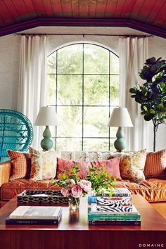 White plaster walls, center arched window flanked by vintage green lamps, turquoise peacock chair, indoor tree, worn leather sofa in orangy rust piled with print pillows in warm colors.