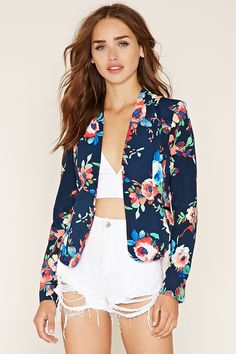 A woven crepe blazer featuring an allover floral print, a collarless design, long sleeves, angled lapels, two faux front pockets, and a hook-eye front closure.