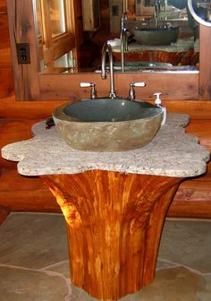 log-cabins:    Sink made from the truck of a tree, with a marble slab formed in the shape of the roots, topped with a granite basin.