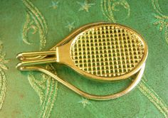 Universal Tennis Racket Tie Clip Vintage Money Clip Extra Large Men's Clothing or Green Back Accessory. A perfect addition to a collection or a gift to that special someone. Maker: unknown Material: gold filled metal Size: see photo Weight: light/medium Condition: In good vintage pre-owned condition. Lovely patina! Boxed for gift giving; gift wrapped on request. These are part of a MASSIVE estate collection of cufflinks and jewelry so be sure to check out our other items here: ...