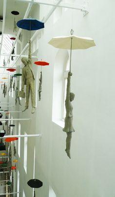 An installation of cement figures dangling from umbrellas inside the EBC office center in Prague by Czech artist Michal Trpák.  See great video --> http://www.michaltrpak.com/cs/