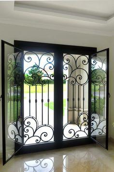 Puerta de hierro forjado con postigos de vidrio Delhierrodesign