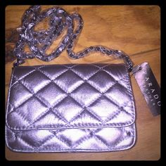 Brand new PARADOX silver quilted handbag! 100% new silver quilted PARADOX small handbag/clutch w tags and original packaging.  Easy to tuck the chain inside the bag to make it a clutch.  Two pockets on the inside with a zippered coin pouch and card slots.  Plenty of room for makeup, $$ and keys.  7 in X 5 in.  Chain measures 42 in.  Perfect for a night out. Paradox Bags Mini Bags