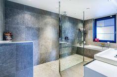 Prachtige badkamer met inloopdouche, grijze tegel. Modern en toch Warm. Badmeubel wc en inbouwbad. Nisje voor toiletspullen