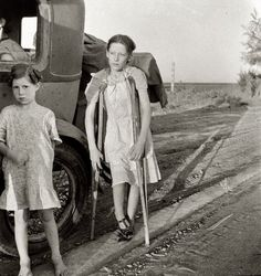 "June 1935. ""Children of Oklahoma drought refugees on highway near Bakersfield, Calif. Family of six; no shelter, no food, no money and almost no gasoline. The child has bone tuberculosis."""