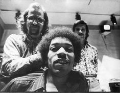 Portrait of American musician Jimi Hendrix (1942 - 1970) (seated), South African-born American music producer and engineer Eddie Kramer (standing left) and studio manager Jim Marron as they pose in the control room of Hendrix's then still under construction Electric Lady Studio, New York, New York, June 17, 1970.
