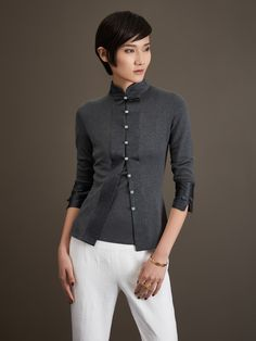 A beautiful modern interpretation of Chinese design, this slim-fitting cardigan has a mandarin collar and natural gemstone buttons. Fashioned from silk cotton, with satin trims, it is one of Shanghai Tang's best loved pieces.  Material: 70% Silk and 30% Cotton  Colour(s): available in H. Grey  Ref: 1C004N3