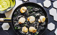 In this Catalan dish, paella rice dyed black with squid ink makes a spectacular backdrop to sautéed scallops and a golden garlic and mustard sauce