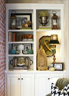 love this bookshelf styling! love the artichokes, the lamp, the birdcage, the silver platter, the lantern, the & ... yeah, everything