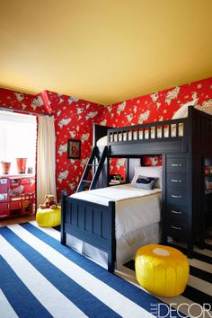 In the boys' bedroom of a colorful East Hampton home, bunk beds by Pottery Barn Kids are dressed in bedding by Sferra. The worldly wallpaper is by Ralph Lauren Home and the rug is by Dash & Albert; the ceiling is painted in Benjamin Moore's American Cheese.