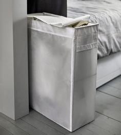 Een smalle witte waszak staat aan het voeteneinde van het bed.