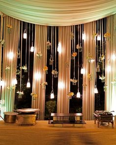 This is one of the prettiest decor  I have ever seen. Love everything about this setup - Mason jar hangings with fairy lights in them, glass bottles with flowers - looks so gorgeous!
