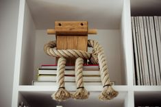 0 little robot in wood and rope in the bookcase