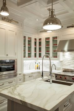 Stunning kitchen with picture lights illuminating glass-front upper cabinets and inset lower cabinets paired with white and grey marble countertops and seamless marble backsplash.