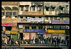 Street with many people waiting in front of closed stores, Old Delhi. New Delhi, India (color)