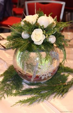 Corporate holiday party, frozen white and blue winter theme! Christmas table centerpiece arrangement with snowflake-filled glass bowl, evergreens, roses, icicle and snowball ornaments | Flowers by Viviano Flower Shop