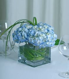With a touch of garden chic, clouds of gorgeous blue hydrangea burst from a clear cube vase. Blue Hydrangea Centerpieces, Purple Wedding Centerpieces, Simple Centerpieces, Party Centerpieces, Wedding Decorations, Popular Flowers, Trendy Wedding, Floral Arrangements, Wedding Flowers