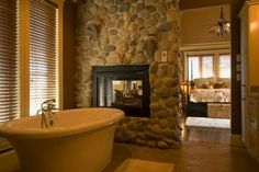river rock fireplace between bathroom and bedroom. gorgeous and comforting